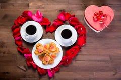 Sur la table en bois, à l'intérieur du coeur des pétales de rose sont deux Photographie stock