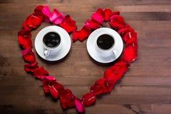 Sur la table en bois, à l'intérieur du coeur des pétales de rose sont deux tasses de café, l'espace de copie est du côté droit Photographie stock