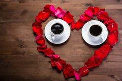 Sur la table en bois, à l'intérieur du coeur des pétales de rose sont deux tasses de café L'espace de copie est du côté gauche Image libre de droits