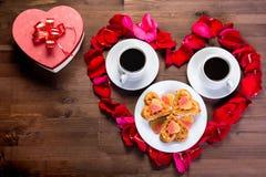 Sur la table en bois, à l'intérieur du coeur des pétales de rose sont deux tasses de café et d'un plat avec des biscuits Du côté  Images libres de droits