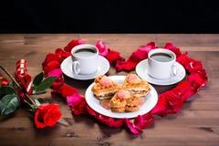 Sur la table en bois, à l'intérieur du coeur des pétales de rose sont deux tasses de café et d'un plat avec des biscuits En dehor Images stock