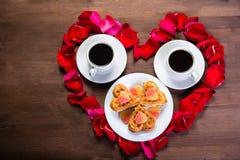 Sur la table en bois, à l'intérieur du coeur des pétales de rose sont deux tasses de café et d'un plat avec des biscuits L'espace Images libres de droits