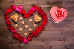 Sur la table en bois est une boîte sous forme de coeur à la droite du coeur des pétales de rose Photographie stock libre de droits