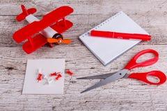 Sur la table en bois sont le bloc-notes, le papier, l'avion de jouet, le marqueur, les brides et les ciseaux Vue supérieure Photos stock