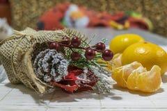 Sur la table est un bouquet décoratif des branches, des baies et des cônes de sapin Sont près les mandarines image stock