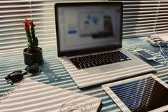 Sur la table est un ordinateur portable ouvert de texture bleu relié qu'à lui le comprimé de telec est près Photo stock