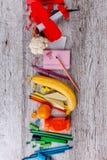 Sur la table une disposition dans une rangée est une chancellerie, un avion rouge de jouet et un morceau de chou-fleur et d'une b Photo stock