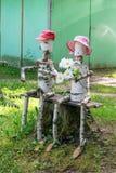 Sur le banc repose un homme et une femme de couples faits de bois Image libre de droits