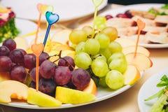 Sur le blanc un plat a coupé en tranches des pommes et des raisins Photographie stock libre de droits