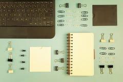 Sur le bleu un fond est un carnet, dans le coin un ordinateur portable Des boutons de Staples et de papier sont d'une manière ord Photographie stock