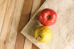 Sur le coin avec la pomme rouge du fruit un de fond de tapis et de fond deux en bois et une poire verte photo libre de droits