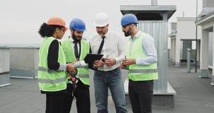 Sur le dessus de toit du groupe de chantier de construction des ingénieurs et de l'architecte tenant la mesure et quelques notes  clips vidéos