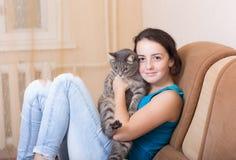 Sur le divan avec un animal familier Photos stock