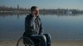 Sur le fauteuil roulant, foi à l'avenir, estropié masculin parlant du téléphone portable, banque de vidéos