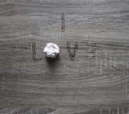Sur le fond en bois est une agrafe de l'amour, au lieu des lettres o par morceau de menthe de papier Image libre de droits