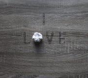 Sur le fond en bois est une agrafe de l'amour, au lieu des lettres o par morceau de menthe de papier Image stock