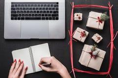 Sur le fond noir, beaucoup de cadeaux et l'ordinateur Sur un livre, les mains du ` un s de dame veulent écrire Photo stock