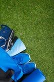 Sur le fond vert de la pelouse, les mensonges des sports bleus mettent en sac avec l'habillement et l'article de sport pour couri images libres de droits