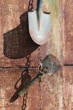 Sur le métal rouillé le mur du village a jeté le coup sur les chaînes a utilisé les outils agricoles de vieux cru photo stock