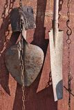 Sur le métal rouillé le mur du village a jeté le coup sur les chaînes a utilisé les pelles agricoles à vieux cru photo libre de droits