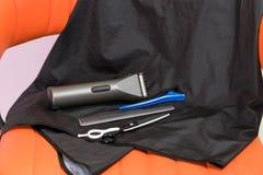 Sur le mensonge orange de chaise les instruments pour couper des cheveux, machine électrique photo libre de droits
