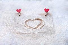 Sur le monticule coeur peint, neige d'imitation, jour du ` s de Valentine, attitudes du ` s de personnes Photos libres de droits
