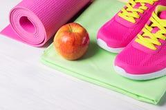 Sur le plancher en bois placez pour le yoga de pratique et une pomme rouge pour un casse-croûte Photographie stock libre de droits
