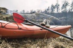 Sur le rivage il y a un kayak sur lequel des espadrilles de configuration et un aviron, Images stock