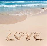 Sur le sable au bord d'océan on lui écrit l'AMOUR Photographie stock