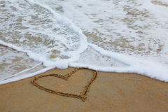 Sur le sable dessiné par coeur Photographie stock