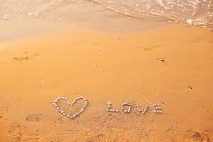 Sur le sable les coquilles ont garni du coeur et de l'amour de mot Images libres de droits