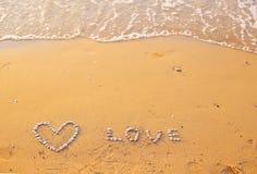 Sur le sable les coquilles ont garni du coeur et de l'amour de mot Image stock