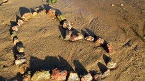 Sur le sable près de l'eau recueillie des pierres du coeur, il obtient le soleil image libre de droits