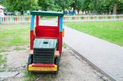 Sur le terrain de jeu, un train multicolore en bois Près de l'allée, herbe verte croissante image libre de droits