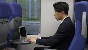 Sur le train l'homme coréen d'affaires travaille sur un ordinateur portable banque de vidéos