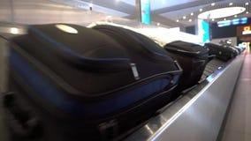 Sur les bagages le carrousel à l'aéroport déplace beaucoup de valises de personnes banque de vidéos