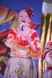 Sur les belles filles d'étape dans des costumes russes nationaux, bains de soleil de robes avec la broderie vibrante - groupe de  Images libres de droits