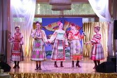 Sur les belles filles d'étape dans des costumes russes nationaux, bains de soleil de robes avec la broderie vibrante - groupe de  Image stock