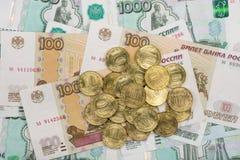Sur les billets de banque aléatoirement dispersés les roubles russes est un groupe de dix-pièce de monnaie Image libre de droits