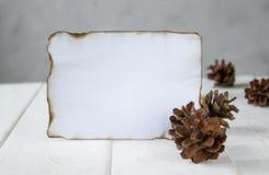 Sur les conseils en bois blancs, une feuille de papier br?l?e le long des bords, c?nes de for?t autour des bords r photo stock