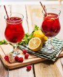 Sur les conseils en bois deux glacent des verres avec le cocktail de framboise rouge Photo stock
