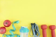 Sur les espadrilles jaunes lumineuses d'un mensonge de fond, les haltères, une corde à sauter et deux pommes Fond de forme physiq Photo libre de droits