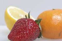 Sur les fruits et les baies de mensonge de table : fraises, citron et mandarine Photos stock