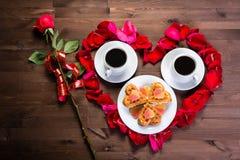 Sur les mensonges de table une rose à la gauche du coeur de l'intérieur de pétales de rose qui sont deux tasses de café Vue de ci Images stock