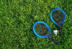 Sur les raquettes bleues du mensonge deux de pelouse d'herbe verte et un cap blanc photos libres de droits