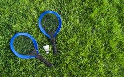 Sur les raquettes bleues du mensonge deux de pelouse d'herbe verte et un cap blanc images stock