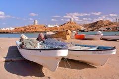 SUR, OMÁN - 7 DE FEBRERO DE 2012: Los barcos de pesca en Ayjah con el reloj se elevan en fondo Fotos de archivo libres de regalías