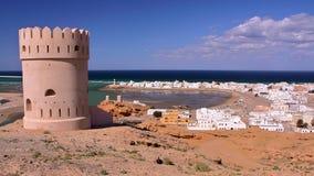 SUR OMAN: Allmän sikt av stranden av Ayjah med ett klockatorn i förgrunden Arkivbild