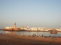 A view taken from Sur in Oman, Arabian peninsula. Lighthouse, dhow and Omani town Stock Photos