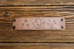 Sur un bracelet en bois brun de table et de cuir avec l'oiseau et les fleurs Photos stock